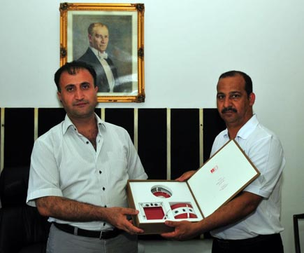 Ali presents Mr Yilmaz a gift from the Bahrain Museum