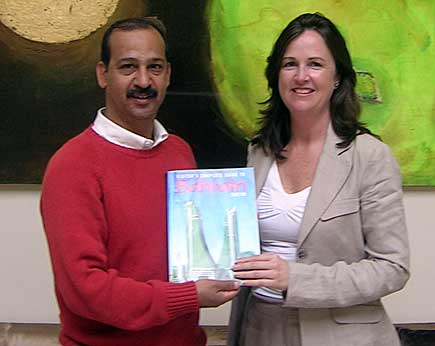 Ali presents Aine with a copy of the Visitor's Complete Guide to Bahrain